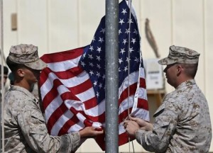U.S. Marines lower their flag during a handover ceremony, as the last U.S. Marines unit and British combat troops end their Afghan operations, in Helmand