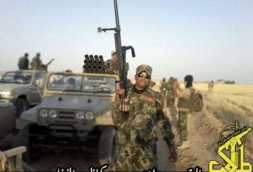 A-man-wearing-Iraqi-army-airborne-jump-wings-with-a-large-calibre-rifle-stands-in-front-of-an-Iranian-Safir-jeep-with-a-107-mm-multiple-rocket-launcher-of-Iraqi-Shia-group-Saraya-Khorasani