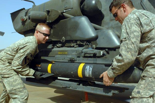 Columbus_Ohio_and_Spc__Scott_Shaver_of_Austin_Texas_load_a_Hellfire_missile_onto_the_mounting_bracket_on_an_AH-64D_Apache_helicopter_here_Oct__1