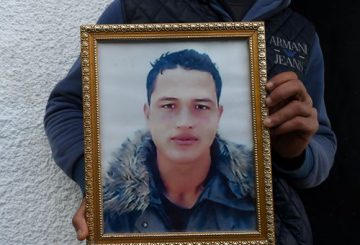 (FILES) This file photo taken on December 23, 2016 shows Walid Amri (back), the brother of 24-year-old Anis Amri, the suspected Berlin truck attacker, posing with a portrait of his brother Anis in front of the family house in the town of Oueslatia, in Tunisia's region of Kairouan. German police on December 28, 2016 detained a Tunisian national on suspicion of having ties to Anis Amri, the suspected Berlin truck attacker gunned down by Italian police, prosecutors said. Twelve people were killed and dozens injured on December 19, when Amri is believed to have hijacked a truck and used it to mow down people at a Berlin Christmas market.  / AFP PHOTO / FETHI BELAID