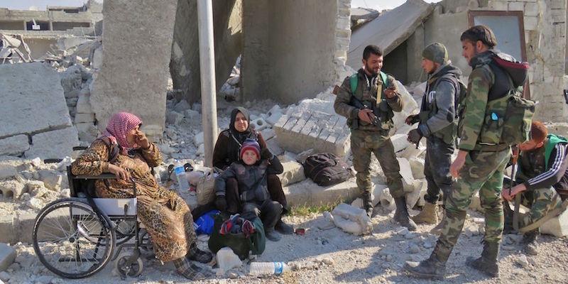 Quattro combattenti fedeli ad Assad insieme a un bambino e due donne residenti nel quartiere Sheikh Saeed di Assad, prima sotto il controllo dei ribelli  (STRINGER/AFP/Getty Images)