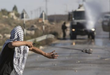FILE - In this Friday, Sept. 18, 2015 file photo, a Palestinian uses a sling shot to throw stones towards Israeli soldiers during clashes in Jalazoun Refugee Camp, near the West Bank city of Ramallah. Israel is struggling with the resurgence of a weapon dating back to David and Goliath: the hurled rock. After an Israeli motorist was killed when his car crashed after being pelted with stones on the eve of the Jewish New Year, the government has pushed for more lenient rules of engagement for police. It is also promised tougher minimum sentences for offenders and heavy fines for minors and their parents. (AP Photo/Majdi Mohammed, File)