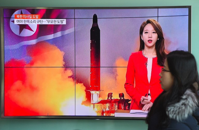 A woman walks past a television screen showing file footage of North Korea's missile launch at a railway station in Seoul on February 12, 2017. North Korea fired a ballistic missile on February 12 in an apparent provocation to test the response from new US President Donald Trump, the South Korean defence ministry said. / AFP PHOTO / JUNG Yeon-Je