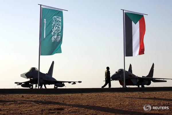 Military personnel walk past the flags of Saudi Arabia and Sudan as Sudan's President Omar Ahmed al-Bashir attends the final training exercise between the Saudi Air Force and Sudanese Air Forces at Merowe Airport in Merowe, Northern State, Sudan April 9, 2017. REUTERS/Mohamed Nureldin Abdallah - RTX34SBQ