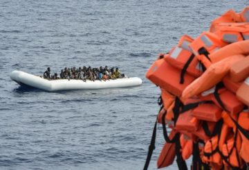 """(FILES) This file photo taken on November 05, 2016 shows migrants and refugees on a rubber boat waiting to be evacuated during a rescue operation by the crew of the Topaz Responder, a rescue ship run by Maltese NGO """"Moas"""" and the Red Cross, on November 5, 2016 off the coast of Libya. Italian Foreign Minister Angelino Alfano on April 29, 2017 said he """"agreed 100 percent"""" with a prosecutor Carmelo Zuccaro who has repeatedly suggested charity boats rescuing migrants in the Mediterranean are colluding with traffickers in Libya. / AFP PHOTO / ANDREAS SOLARO"""