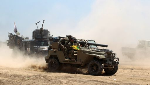 Iraqi government forces advance near al-Sejar village, north-east of Fallujah, on May 26, 2016, as they take part in a major assault to retake the city from the Islamic State (IS) group. Tens of thousands of security forces are deployed in the Fallujah area for an assault aimed at retaking the city from the Islamic State group. Fallujah, which lies only 50 kilometres (30 miles) west of Baghdad, has been out of government control since January 2014 and is one of only two remaining major Iraqi cities still in IS hands, the other being Mosul. / AFP PHOTO / AHMAD AL-RUBAYE