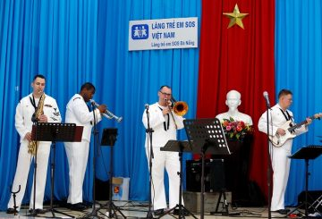 Members of U.S. Seventh Fleet Band perform as a statue of late Vietnamese revolutionary leader Ho Chi Minh is seen in the background, as part of the U.S aircraft carrier USS Carl Vinson to Vietnam, at the Da Nang SOS Children's Village in Danang, Vietnam March 6, 2018. REUTERS/Kham