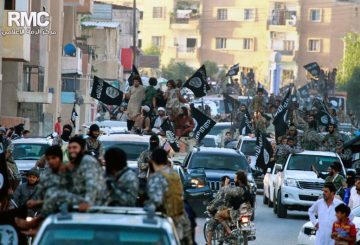 FILE - In this undated file image posted on Monday, June 30, 2014, by the Raqqa Media Center of the Islamic State group, a Syrian opposition group, which has been verified and is consistent with other AP reporting, fighters from the Islamic State group parade in Raqqa, north Syria. In the early dawn of Nov. 2, militant leaders with the Islamic State group and al-Qaida gathered at a farm house in northern Syria and sealed a deal to stop fighting each other and work together against their opponents, a prominent Syrian opposition official and a rebel commander said. Such an alliance could be a significant blow to struggling U.S-backed Syrian rebels. (AP Photo/Raqqa Media Center of the Islamic State group, File)