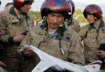 FILE - In this Tuesday, Aug. 16, 2005 file photo, wearing a flying gear Russian President Vladimir Putin holds his souvenir, a mock-up of a supersonic Tu-160 strategic bomber, at an airfield near the northern city of Murmansk, Russia, shortly after landing there aboard a Tu-160, with the bomber crew in the background. Russia's defense minister says the military will conduct regular long-range bomber patrols, ranging from the Arctic Ocean to the Caribbean and the Gulf of Mexico. (AP Photo/ITAR-TASS, Presidential Press Service, Alexei Panov)