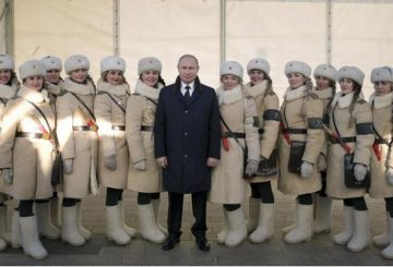 President Vladimir Putin, center, poses for a picture alongside with women dressed in historic Red Army uniforms during commemorations of the 75th anniversary of the Battle of Stalingrad in the southern Russian city of Volgograd, once known as Stalingrad, Russia, Friday, Feb. 2, 2018. The five months of fighting in Stalingrad between August 1942 and February 1943 is regarded as the bloodiest war battle in history. The death toll for soldiers and civilians was about 2 million. Most of the city was reduced to rubble before Nazi forces surrendered on Feb. 2, 1943. (Alexei Druzhinin, Sputnik, Kremlin Pool Photo via AP)