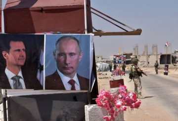 Members of Russian and Syrian forces stand guard near posters of Syrian President Bashar al-Assad and his Russian counterpart Vladimir Putin at the Abu Duhur crossing on the eastern edge of Idlib province on August 20, 2018. - Civilians are coming from rebel-held areas in Idlib province and entering regime-held territories through the Abu Duhur crossing, some of them returning to their villages that were recaptured by the regime forces earlier this year. (Photo by George OURFALIAN / AFP)