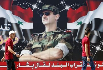 "Syrian youths walk past a billboard showing a picture of Syrian President Bashar al-Assad wearing sunglasses while dressed in a Field Marshal's camouflage fatigues, on display in the centre of the capital Damascus on July 9, 2018, with a caption below reading in Arabic: ""If the country's dust speaks, it will say Bashar al-Assad."" / AFP PHOTO / LOUAI BESHARA"