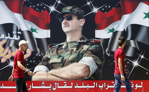"""Syrian youths walk past a billboard showing a picture of Syrian President Bashar al-Assad wearing sunglasses while dressed in a Field Marshal's camouflage fatigues, on display in the centre of the capital Damascus on July 9, 2018, with a caption below reading in Arabic: """"If the country's dust speaks, it will say Bashar al-Assad."""" / AFP PHOTO / LOUAI BESHARA"""