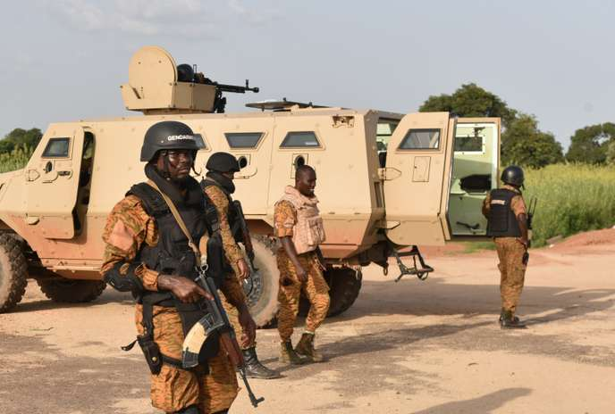 "Burkinabe soldiers stand in position near the Presidental Security Regiment (RSP) military barracks on September 29, 2015 in Ouagadougou. Burkina Faso's government on September 28 accused an elite presidential guard, led by coup leader Gilbert Diendere, behind this month's week-long coup of refusing to disarm, of seizing loyalist troops, and of planning yet more trouble. ""The disarmament process started Saturday (September 26) was forcably questioned by General Diendére who informed his elements that the RSP can not be dissolved by the transitional goverment and it was better to resist,"" according to a government statement. AFP PHOTO / SIA KAMBOU"