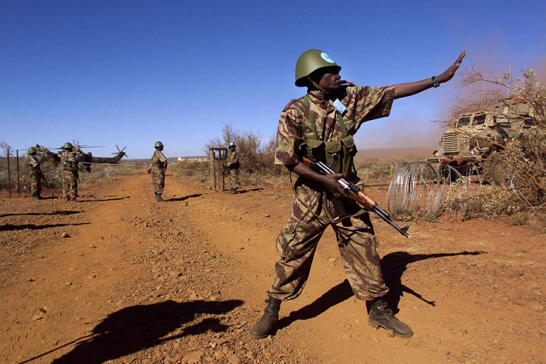 """A Mozambican soldier directs traffic at a checkpoint during an excercise 22 April in Lahatla army camp in the Northern Cape province, some 600 km west of Johannesburg. Soldiers from 12 South African development community (SADC) countries participated in the excercise """"Blue crane"""" to coordinate and train for future peacekeeping operations. (ELECTRONIC IMAGE) / AFP / ODD ANDERSEN"""