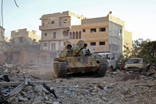"A member of the self-styled Libyan National Army, loyal to the country's east strongman Khalifa Haftar, rides in a tank as it drives down a street through the rubble in Benghazi's central Akhribish district on July 19, 2017 following clashes with militants. Libyan military strongman Khalifa Haftar on July 5, 2017 announced the ""total liberation"" of second city Benghazi, which was overrun by jihadists three years prior. / AFP PHOTO / Abdullah DOMA"