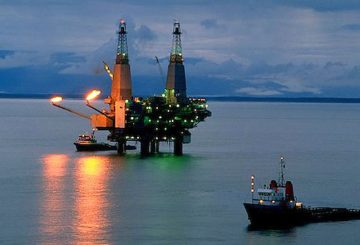 Alaska. Cook Inlet. Dolly Varden off shore oil rig. Oil drilling platform at night with work boats.