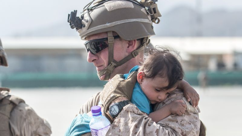 US Marine calms an infant during an evacuation at Hamid Karzai International Airport, Kabul, Afghanistan v2 210821 CREDIT US DEPARTMENT OF DEFENSE
